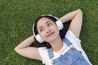 cute-indonesian-girl-with-headphones-laying-on-the-grass 1437-731