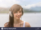 young-woman-wearing-headphones-at-lakeside-under-bright-sunlight-EA05F7