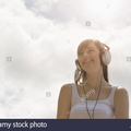 young-woman-wearing-headphones-under-bright-sunny-sky-EA05FB