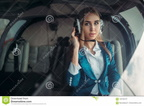 female-pilot-headphones-helicopter-cabin-female-pilot-headphones-poses-helicopter-cabin-hangar-interior-background-125100137